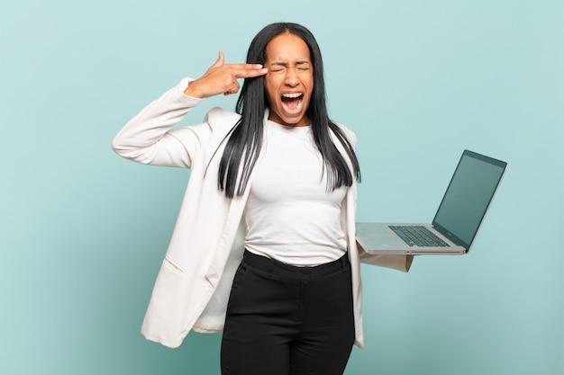 Jeune femme noire à l'air malheureuse et stressée, geste de suicide faisant un signe d'arme à feu avec la main, pointant vers la tête. concept d'ordinateur portable