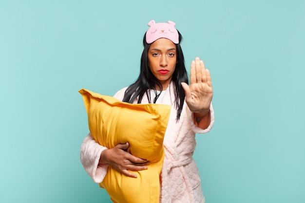 Jeune femme noire à l'air sérieuse, sévère, mécontente et en colère montrant la paume ouverte faisant un geste d'arrêt. concept de pyjama