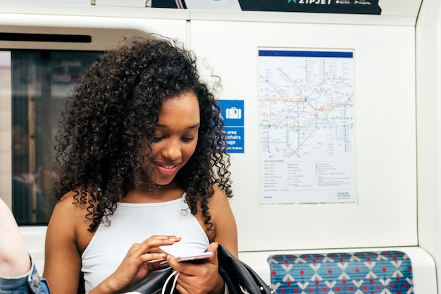 Jeune femme noire assise à l'intérieur du métro sur le téléphone mobile