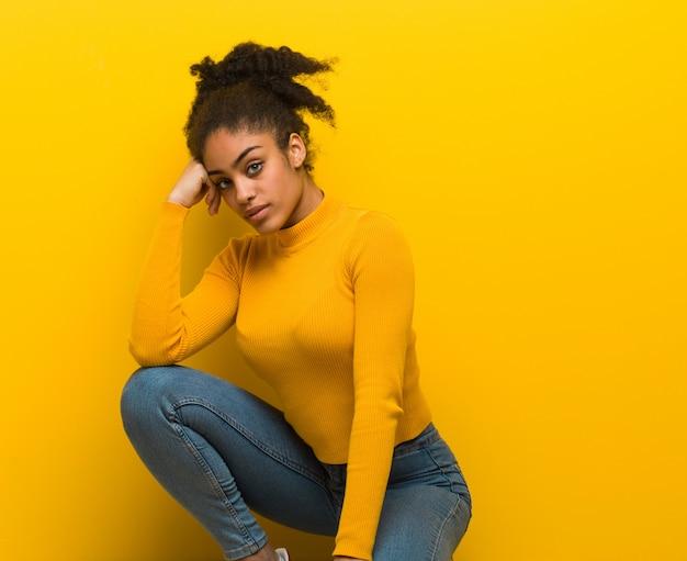 Jeune femme noire assise sur un mur orange