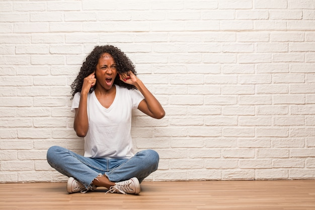 Jeune femme noire assise sur un plancher en bois, couvrant les oreilles avec les mains, en colère et fatiguée d'entendre du son