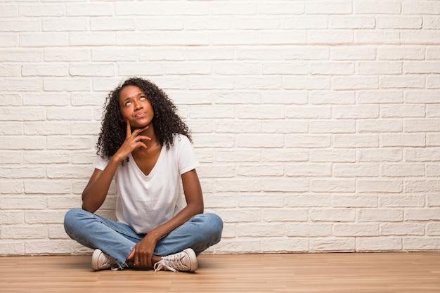 Jeune femme noire assise sur un plancher en bois doutant et confus, pensant à une idée ou inquiète de quelque chose