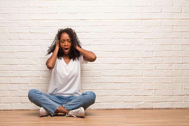 Jeune femme noire assise sur un plancher en bois frustrée et désespérée