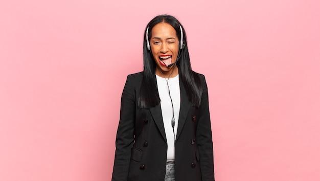 Jeune femme noire à l'attitude joyeuse, insouciante, rebelle, plaisantant et tirant la langue, s'amusant. concept de télémarketing