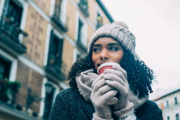Jeune femme noire buvant du café errant dans les rues de madrid en hiver