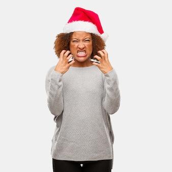 Jeune femme noire coiffée d'un bonnet de noel en colère et contrariée