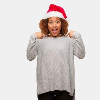 Jeune femme noire coiffée d'un bonnet de noel surprise, réussie et prospère