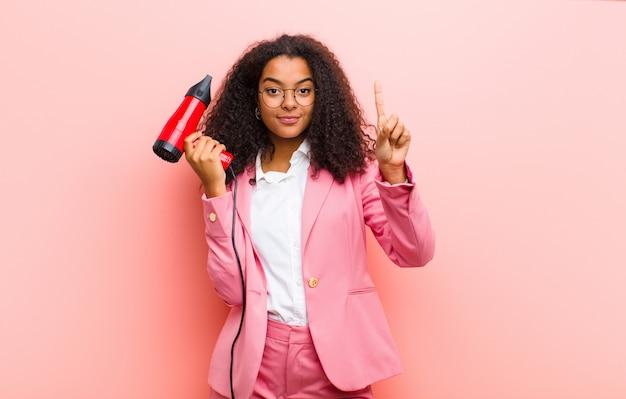 Jeune femme noire avec un coiffeur sur mur rose