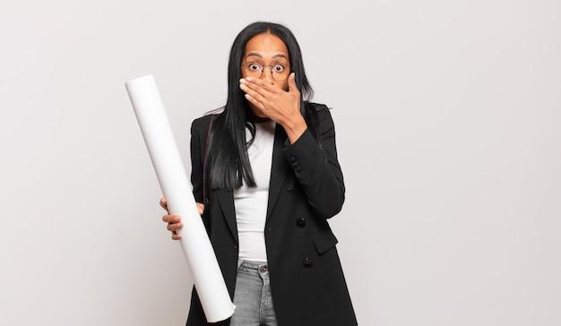 Jeune femme noire couvrant la bouche avec les mains avec une expression choquée et surprise, gardant un secret ou disant oups. concept d'architecte