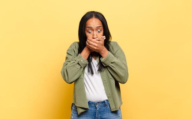 Jeune femme noire couvrant la bouche avec les mains avec une expression choquée et surprise, gardant un secret ou disant oups