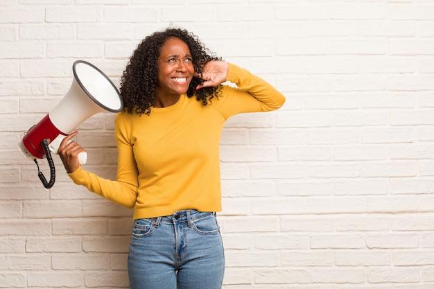 Jeune femme noire couvrant les oreilles avec les mains, en colère et fatiguée d'entendre du son