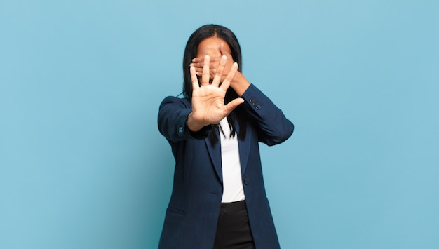 Jeune femme noire couvrant le visage avec la main et mettant l'autre main devant pour arrêter la caméra, refusant les photos ou les images. concept d'entreprise