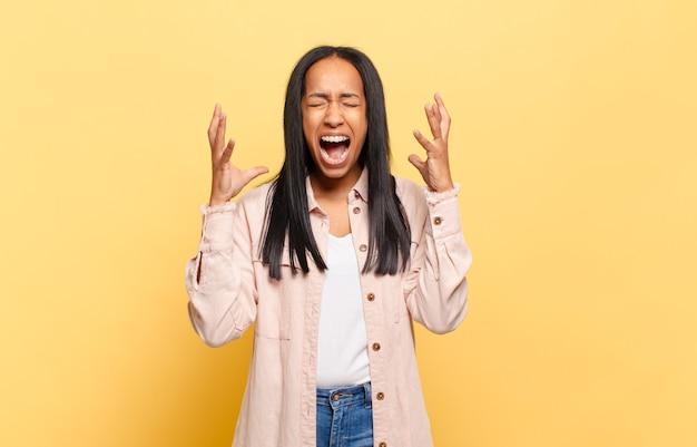 Jeune femme noire criant furieusement, se sentant stressée et ennuyée avec les mains en l'air disant pourquoi moi