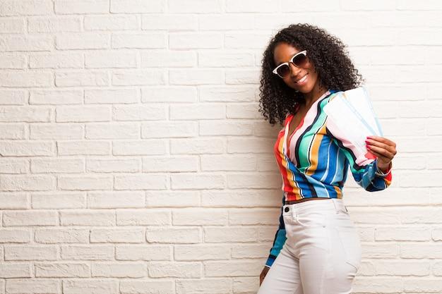 Jeune femme noire croisant les bras, souriante et heureuse, confiante et amicale