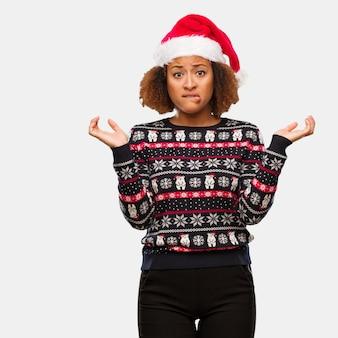 Jeune femme noire dans un pull de noël à la mode avec une impression confuse et douteuse