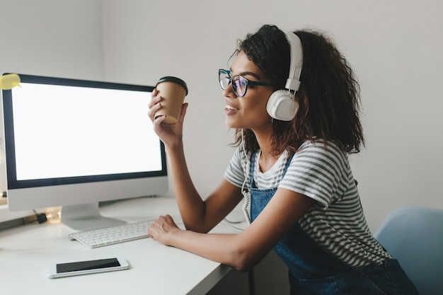 Jeune femme noire en détournant les yeux avec nostalgie tenant une tasse de café et souriant tout en travaillant au bureau