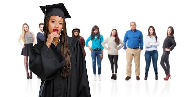 Jeune femme noire diplômée portant des tresses doutant et confus