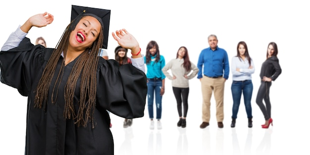 Jeune femme noire diplômée, portant des tresses écouter de la musique, danser et s'amuser, bouger, crier et exprimer son bonheur, concept de liberté
