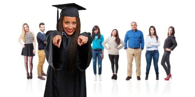 Jeune femme noire diplômée portant des tresses gaies et souriantes pointant vers l'avant