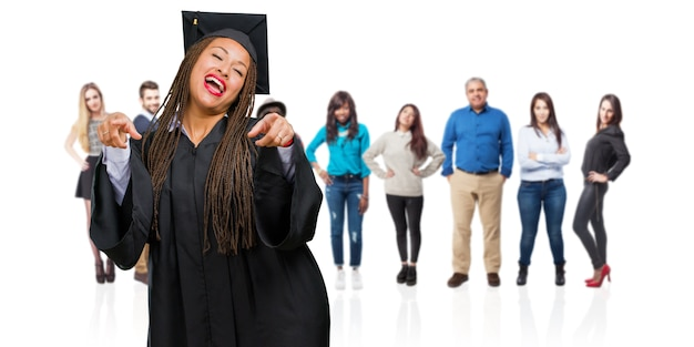 Jeune femme noire diplômée portant des tresses pointant sur le côté, souriante surprise présentant quelque chose de naturel et décontracté