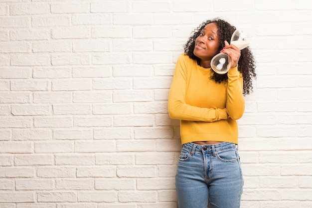 Jeune femme noire doutant et haussant les épaules, concept d'indécision et d'insécurité, incertain de quelque chose