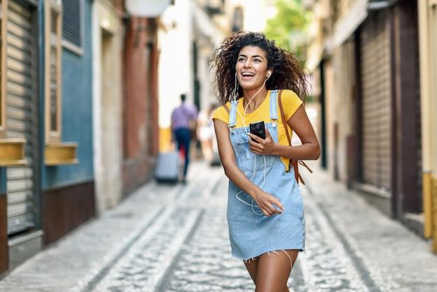 Jeune femme noire, écouter de la musique avec des écouteurs à l'extérieur