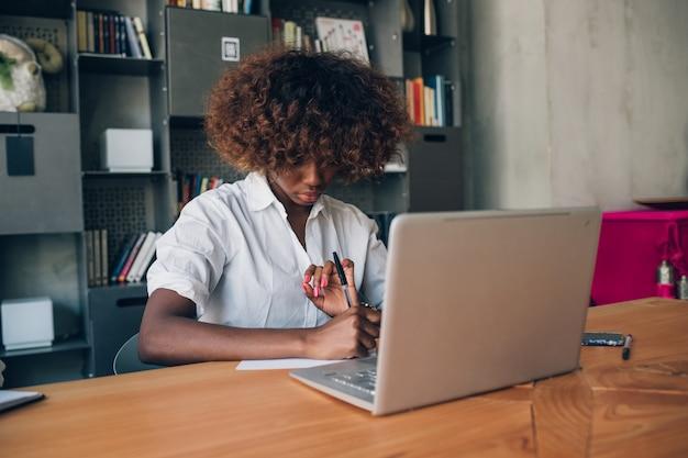 Jeune femme noire écrit et utilisant un ordinateur portable