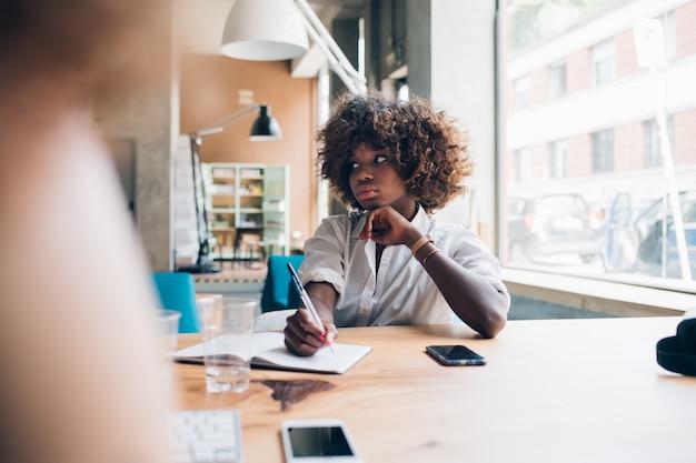 Jeune femme noire écrivant lors d'une réunion