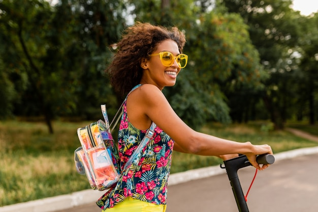 Jeune femme noire élégante s'amusant dans le parc à cheval sur un scooter électrique dans le style de la mode estivale, tenue hipster colorée, portant un sac à dos et des lunettes de soleil jaunes
