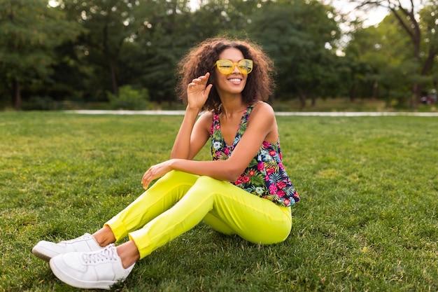 Jeune femme noire élégante s'amusant dans le style de mode d'été du parc, tenue de hipster coloré, assis sur l'herbe portant des lunettes de soleil jaunes et un pantalon, des baskets