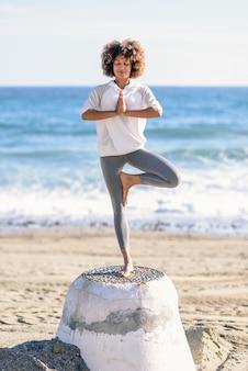 Jeune femme noire, faire du yoga sur la plage.