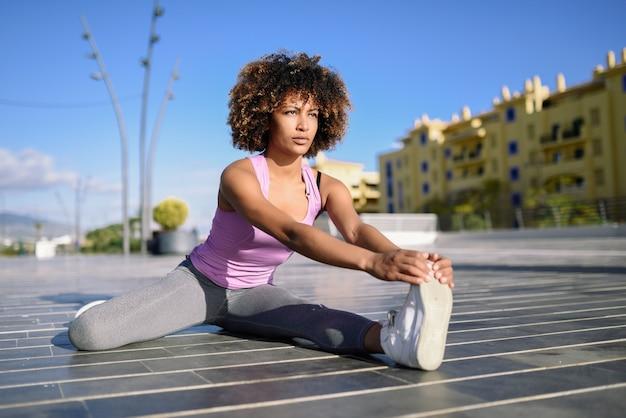 Jeune femme noire faisant des étirements après avoir couru à l'extérieur