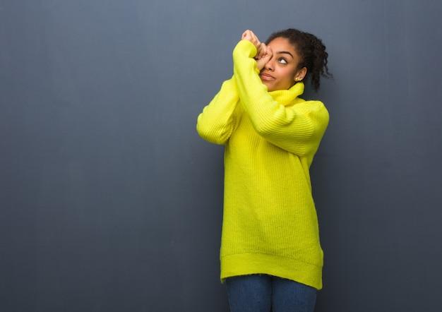 Jeune femme noire faisant le geste d'une longue-vue