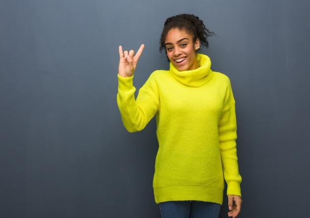 Jeune femme noire faisant un geste rock