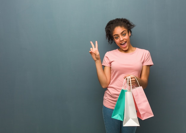 Jeune femme noire faisant un geste de victoire elle tient un sac à provisions.