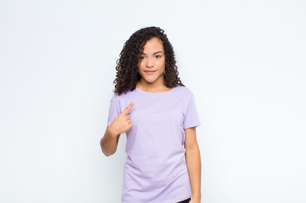 Jeune femme noire à la fierté, confiante et heureuse, souriante et pointant vers soi ou faisant signe numéro un sur le mur blanc