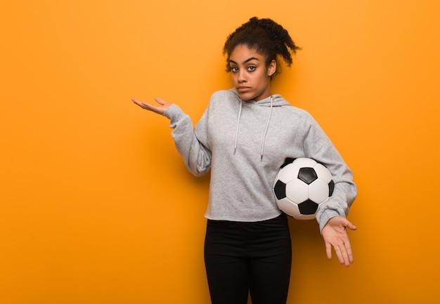 Jeune femme noire fitness confuse et douteuse. tenir un ballon de foot.