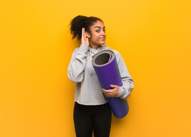 Jeune femme noire fitness essaie d'écouter un commérage. tenant un tapis.
