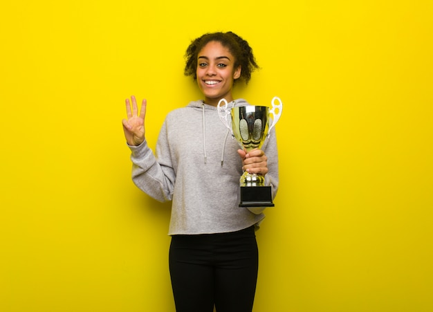 Jeune femme noire de fitness montrant le numéro trois. tenant un trophée.