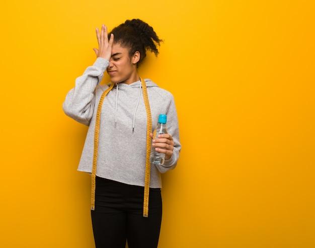 Jeune femme noire fitness, oublieuse, réalise quelque chose. elle tient une bouteille d'eau.