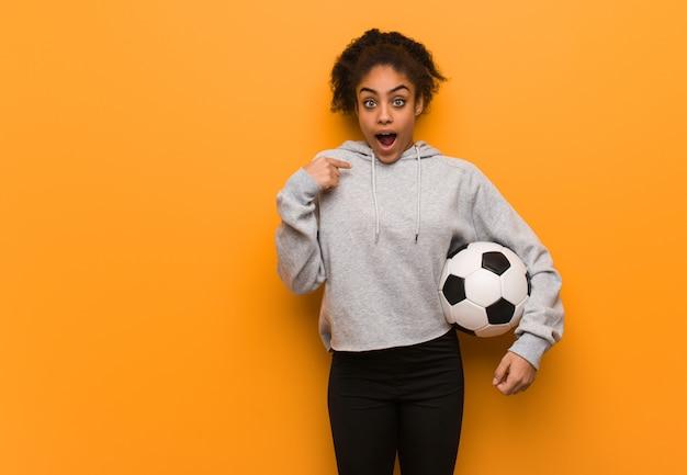 Jeune femme noire fitness, surprise, réussie et prospère. tenir un ballon de foot.