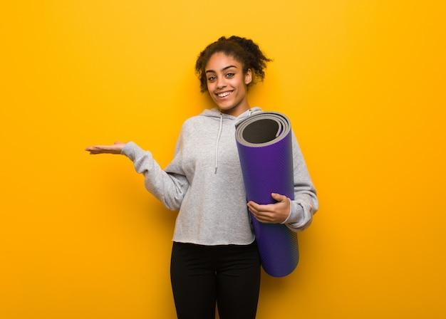 Jeune femme noire fitness tenant quelque chose avec la main. tenant un tapis.
