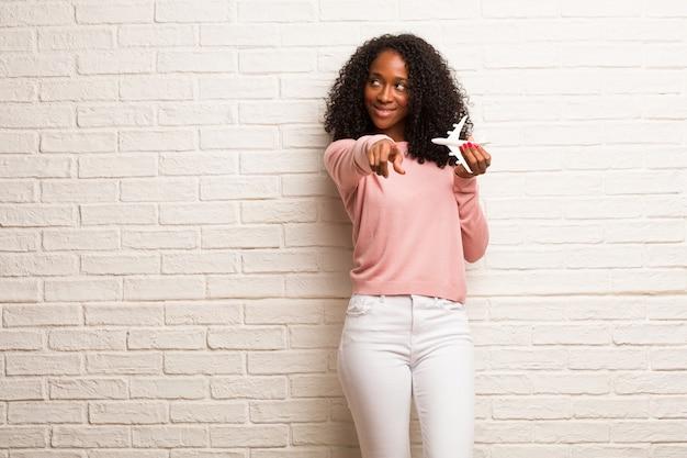 Jeune femme noire gaie et souriante pointant vers l'avant
