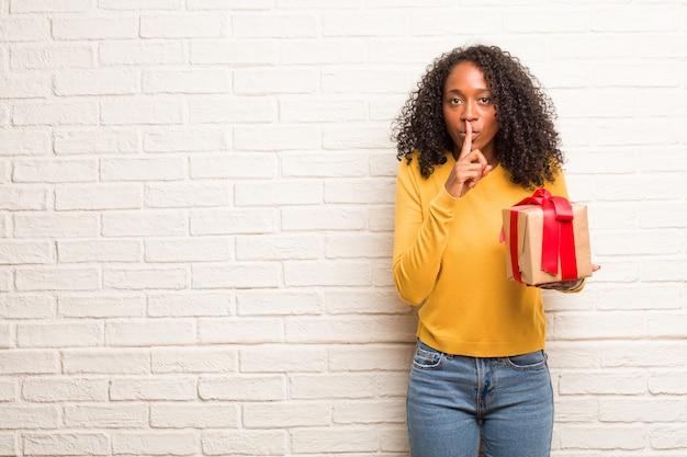 Jeune femme noire gardant un secret ou demandant le silence, visage sérieux, concept d'obéissance
