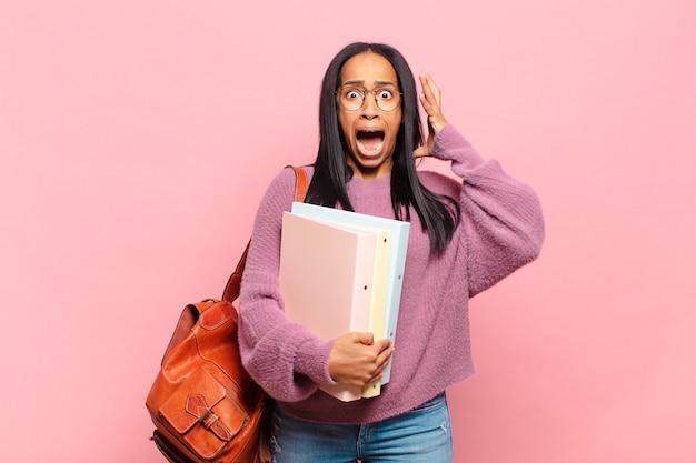 Jeune femme noire hurlant les mains en l'air, se sentant furieuse, frustrée, stressée et bouleversée. concept étudiant