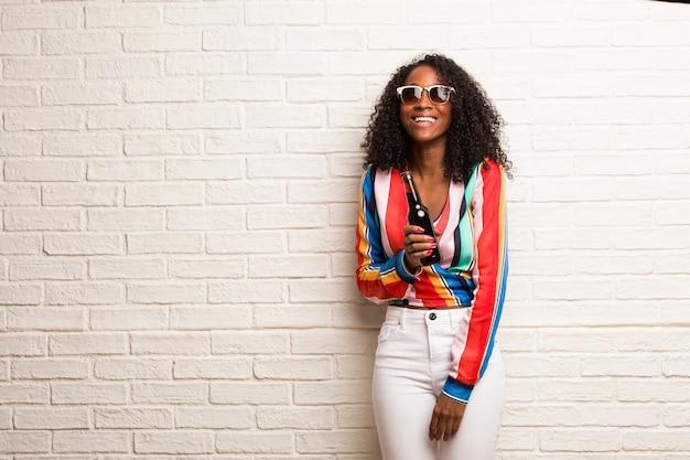 Jeune femme noire levant les yeux, pensant à quelque chose d'amusant et ayant une idée, concept d'imagination, heureuse et excitée