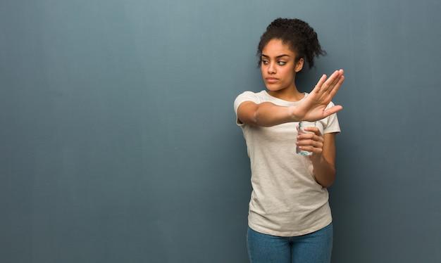 Jeune femme noire mettant la main devant elle tient une bouteille d'eau.