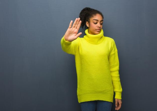 Jeune femme noire mettant la main devant