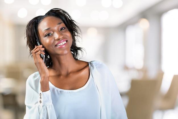Jeune femme noire parlant au téléphone