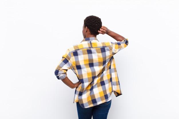 Jeune femme noire pensant ou doutant, se grattant la tête, se sentant perplexe et confus, vue arrière ou arrière